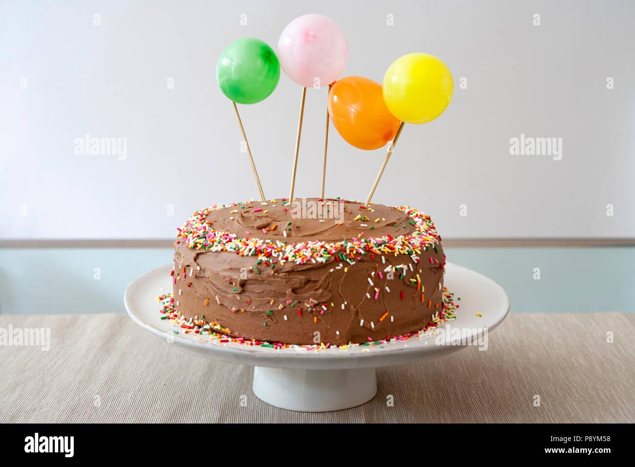 Geburtstag Kuchen mit Schokoladenglasur dekoriert mit Ballons und Streuseln Stockbild