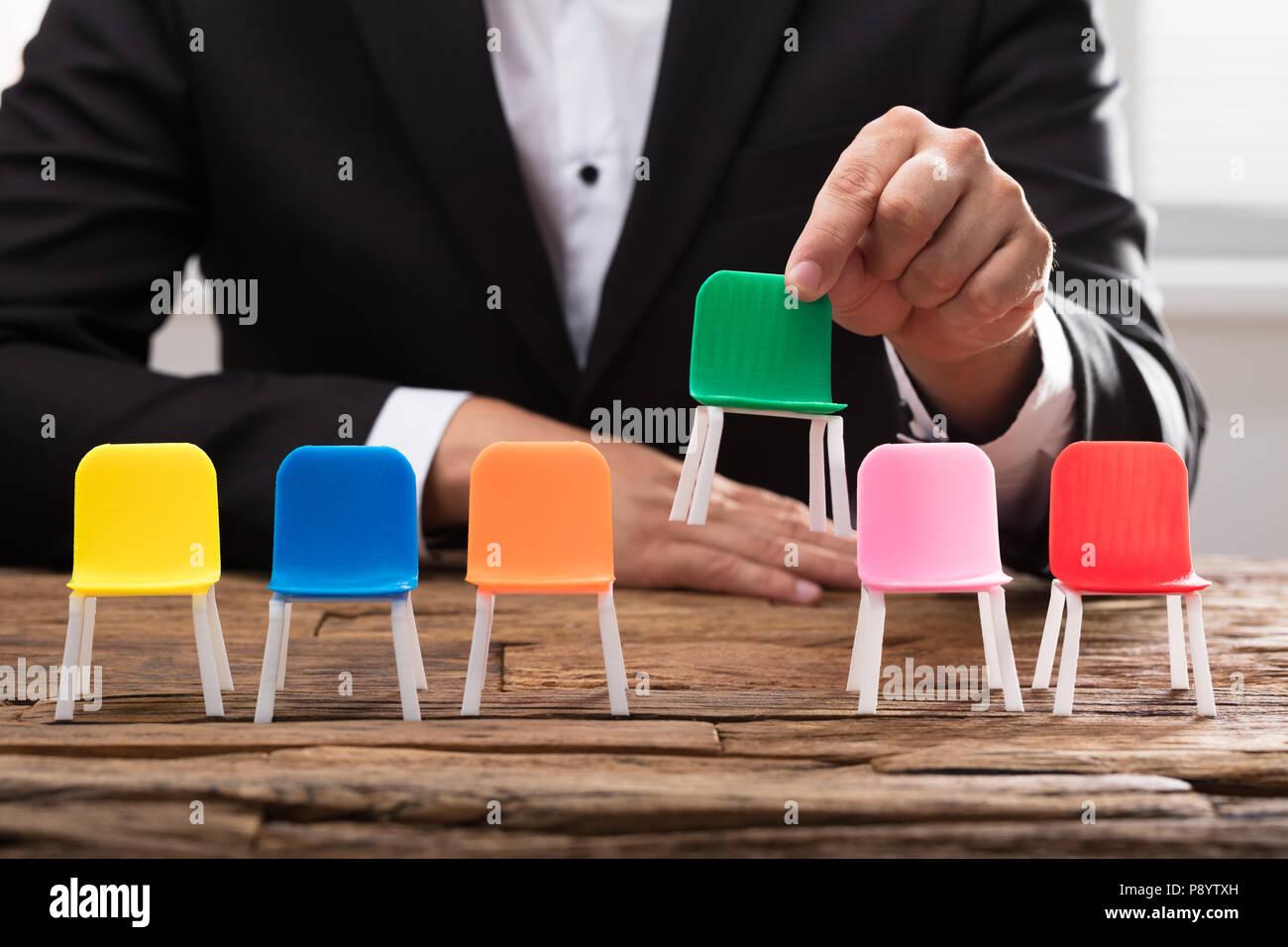 Der Geschäftsmann, der von Hand gepflückt, grünen Stuhl unter anderem auf hölzernen Schreibtisch Stockbild