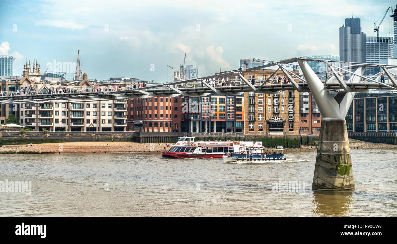 Fußgänger die Millenium Bridge fka Wackelbrücke, zwei Sightseeing Boote Sarah Kathleen & Millenium Zeit unterqueren mit Passagieren überschreiten. Stockbild