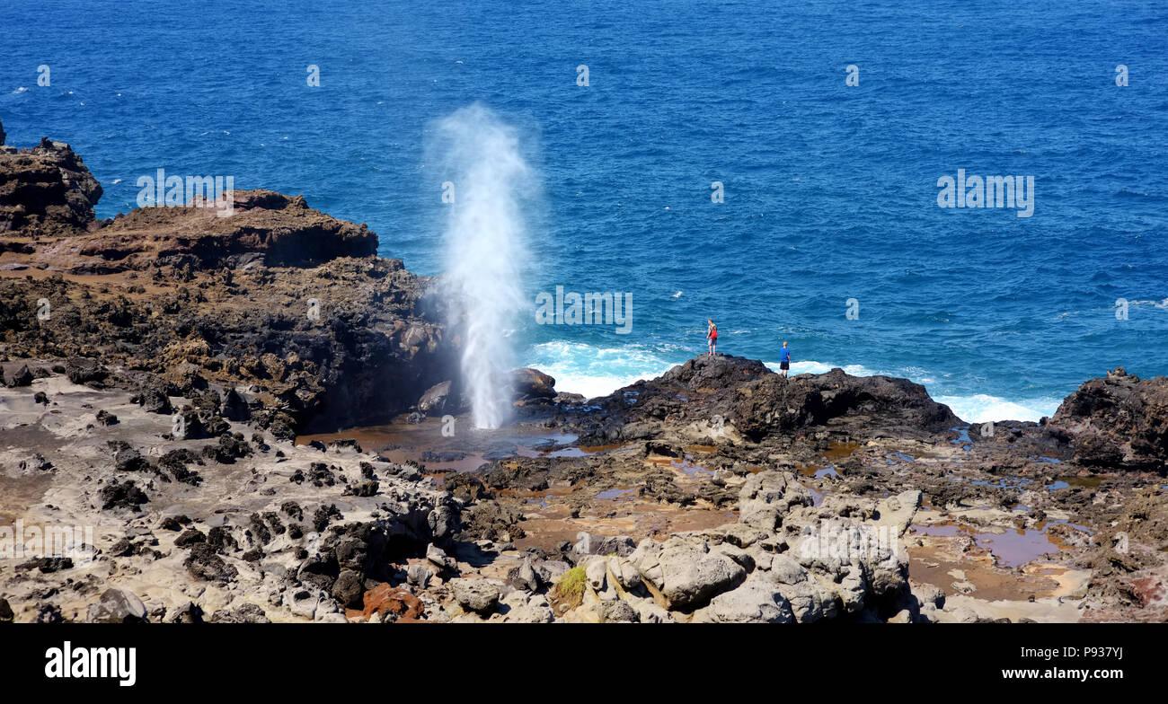 Touristen bewundern die Nakalele blowhole an der Küste von Maui. Ein Strahl von Wasser und Luft ist heftig, durch das Loch in den Felsen gezwungen. Hawaii, U Stockbild