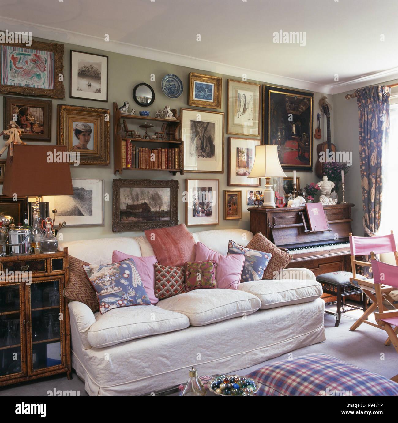 Große Sammlung von Bildern an der Wand über dem weißen Sofa mit ...