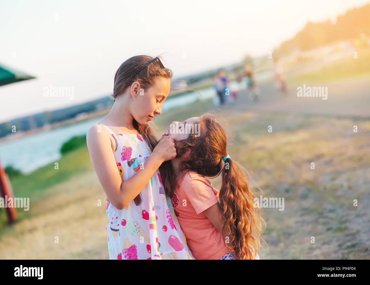 Zwei glückliche kleine Mädchen Spaß haben und sich an der Wiese im Sommer Tag Stockfoto