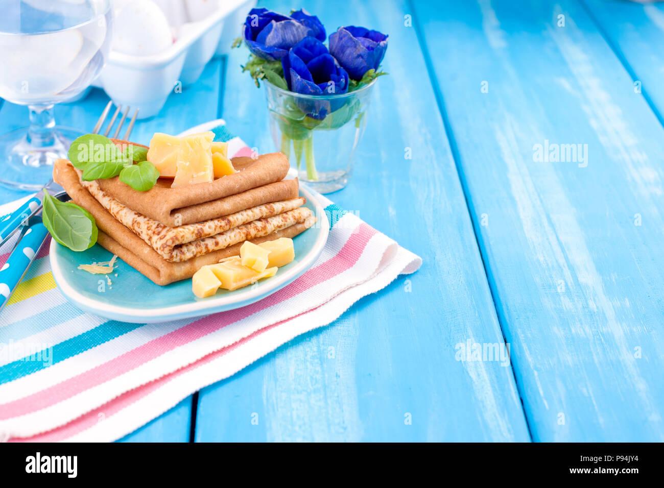 Hausgemachte Pfannkuchen mit Parmesan und Basilikum für Spring Carnival. Italienisches Frühstück. Helle Blumen Tulpen. Blauen Hintergrund. Ein freier Platz für Text oder eine Postkarte. Stockbild