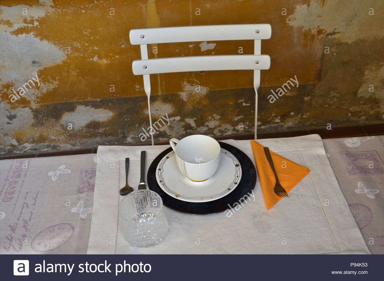 Tabelle Einstellung für ein, ockerfarbenen Hintergrund, mittelalterliches Haus Fassade, Alte, Frühstück, Gerichte, Orange, Weiß, Geschirr, Lombardei, Italien Stockbild
