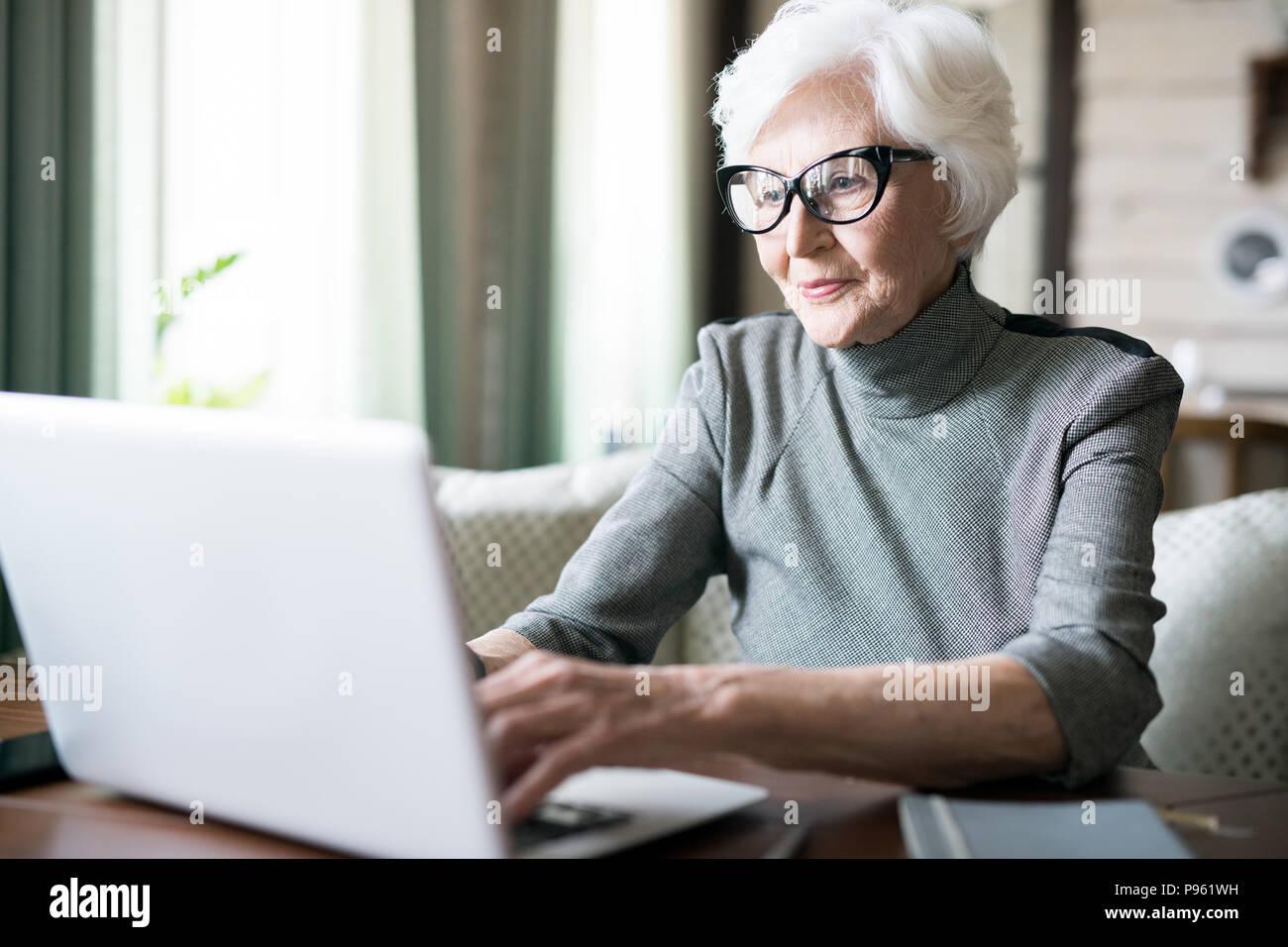 Ältere Frau, die Eingabe auf laptop Stockbild