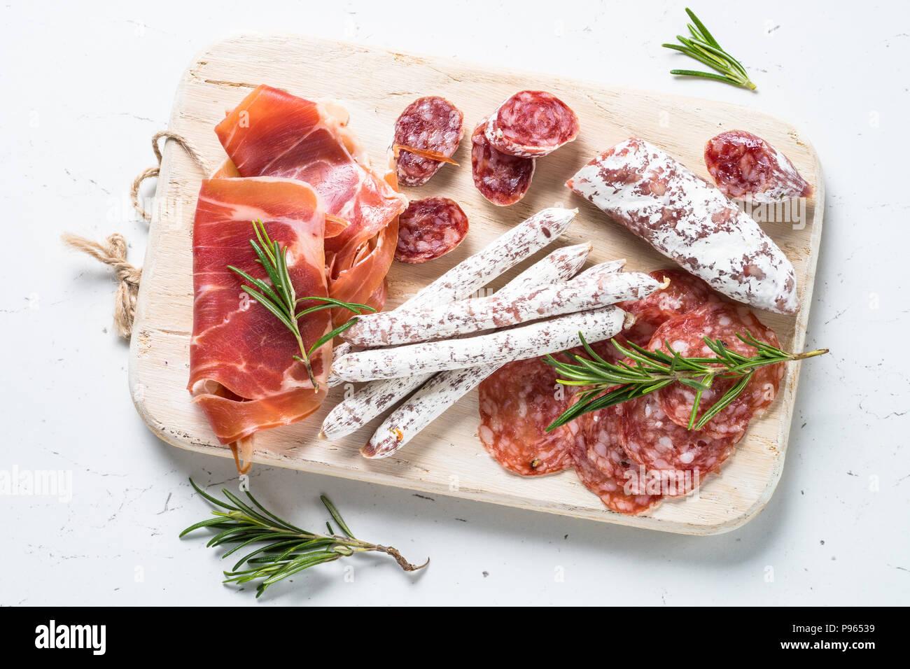 Antipasti. Traditionelle italienische Antipasti, geschnittenes Fleisch, Vorspeisen auf Holz Schneidebrett auf weißem Tabelle, Ansicht von oben. Stockbild