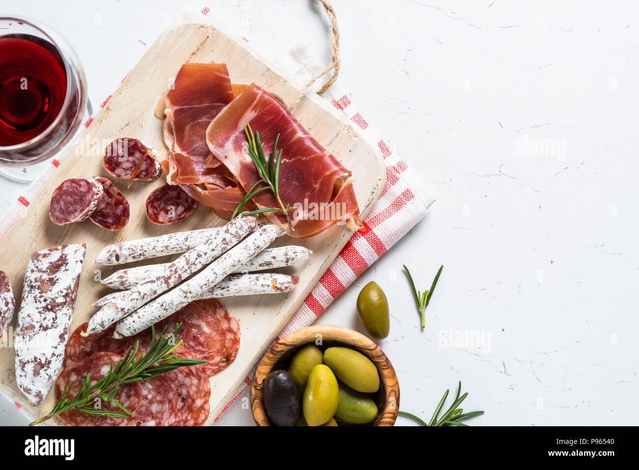 Traditionelle italienische Antipasti, in Scheiben geschnittene Fleisch mit Wein und Oliven auf weißen Tisch gesetzt. Ansicht von oben, kopieren. Stockbild