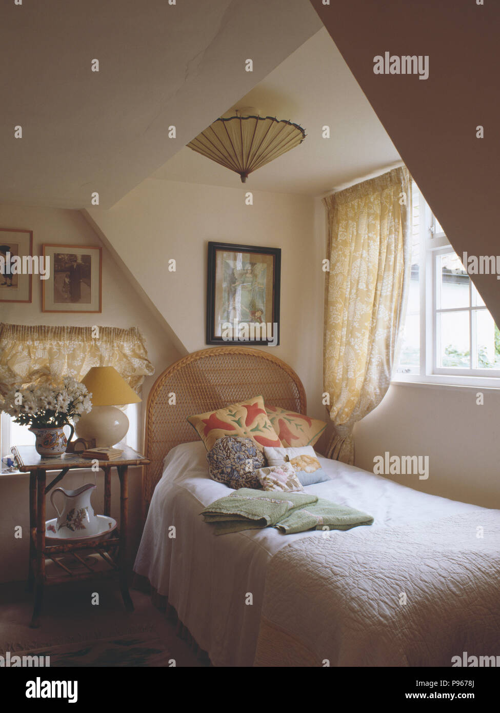 Bambus-Tisch neben Einzelbett unter Fenster im Dachgeschoss ...