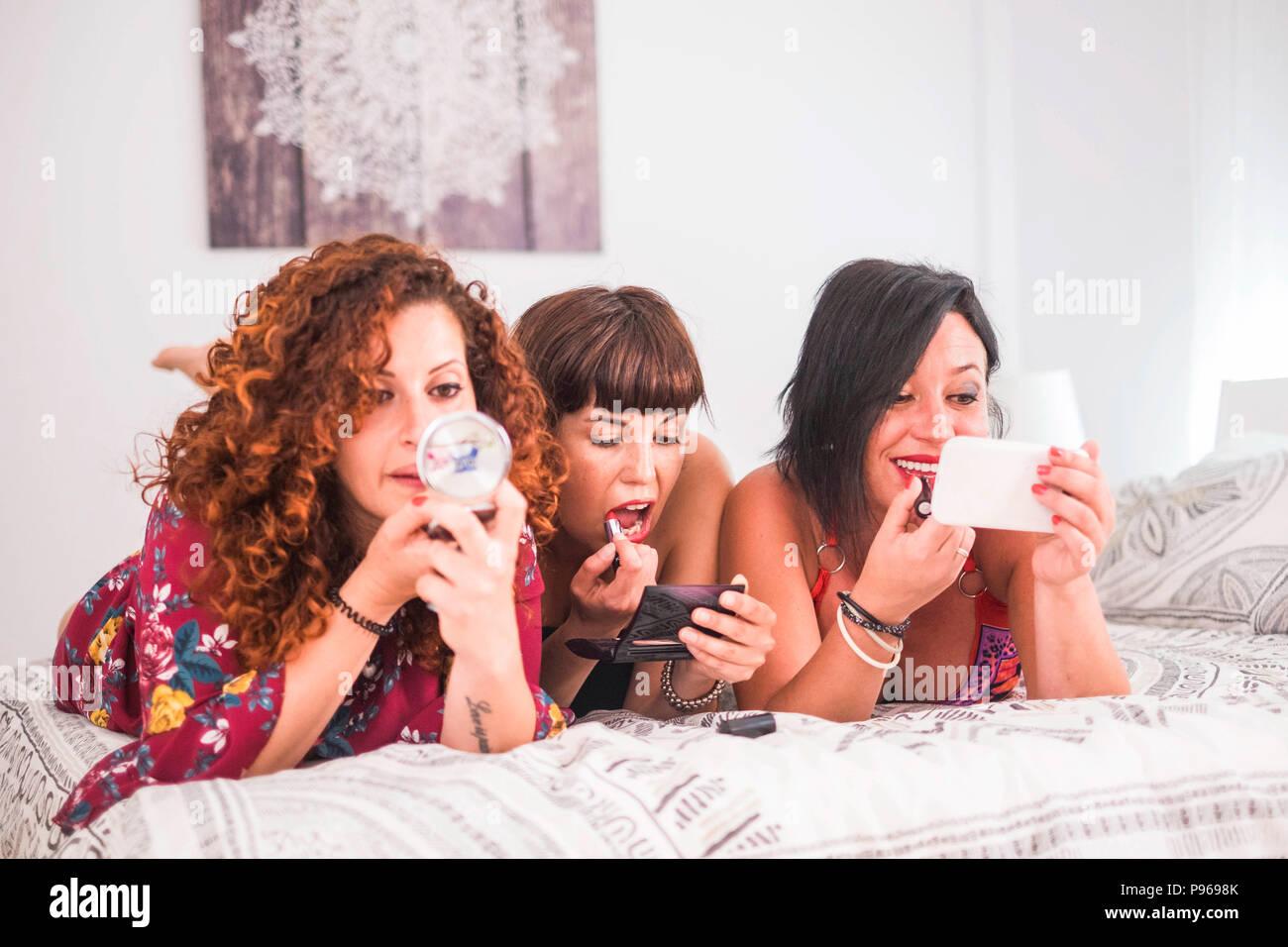 Drei Frauen, die Freunde zu tun zu Hause in Freundschaft legte sich auf das Bett im Schlafzimmer. Machen schön und Schönheit für die jungen kaukasischen Frauen Stockbild