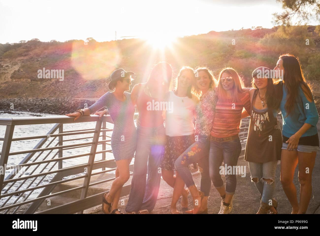 Gruppe von Sieben und schönen kaukasische Mädchen, junge Frauen, die Spaß haben und Lachen und Lächeln im Freien in der Nähe des Ozeans während des Sonnenuntergangs. Hintergrundbeleuchtung paople Stockbild