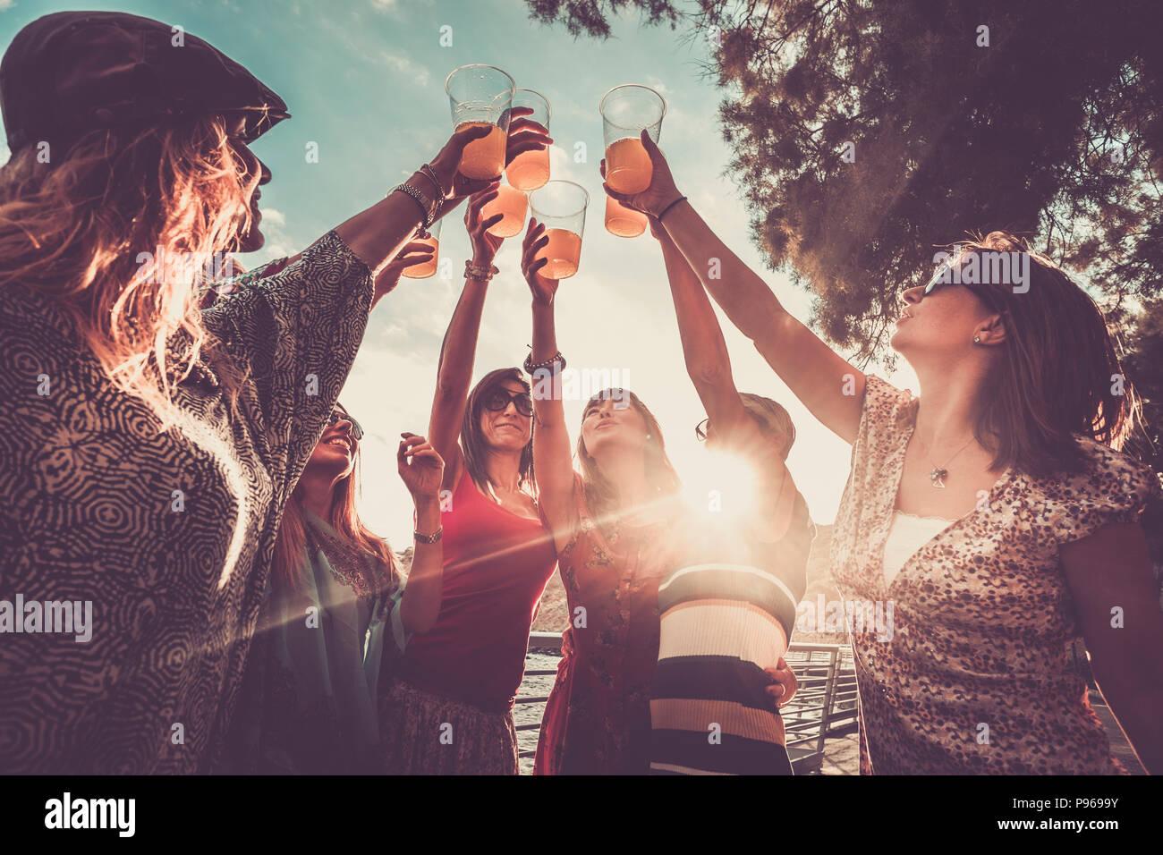 Feiern Freundschaft oder Erfolg Team arbeitet im Freien mit farbigen Saft und 7 schöne weibliche Freunde alle zusammen mit orange Cocktail und die sunl Stockbild