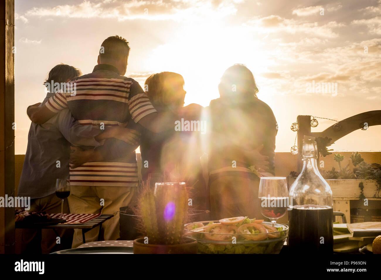 Menschen Gruppe von älteren Freunden Umarmung und zusammen großartig Anzeigen der golde Sonnenuntergang von der Dachterrasse. Wohnen immer in Urlaub und Ruhestand happi Stockbild