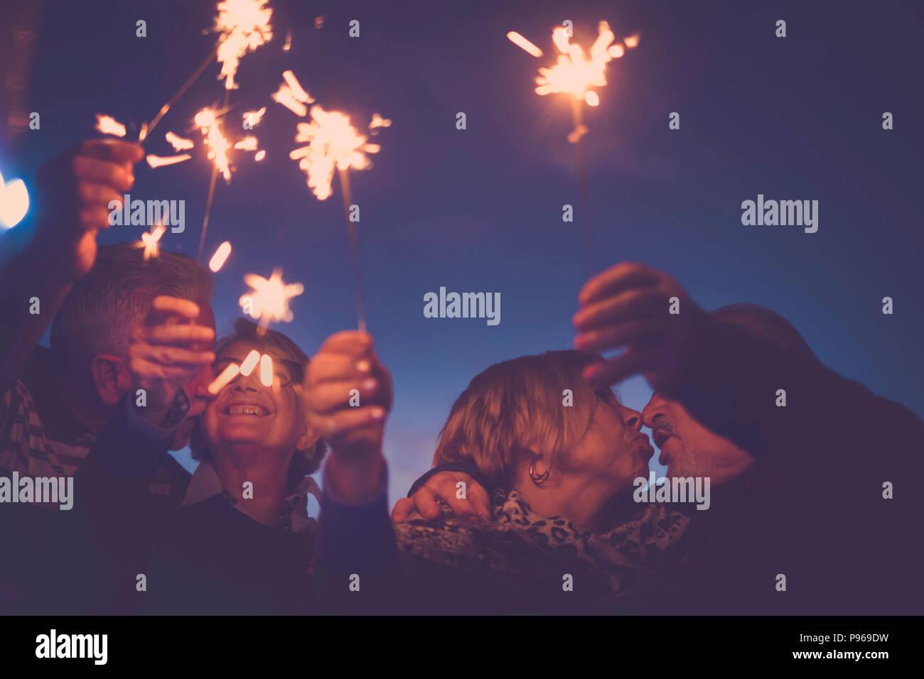 Feier Party für Urlaub Nacht oder Silvester 2019. Gruppe älterer Männer und Frauen, die Menschen mit Feuer Funken. Jeder küssen und mit viel f Stockbild