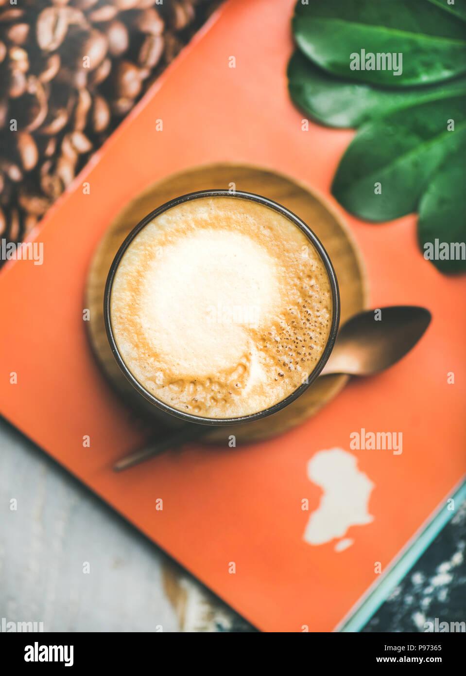 Cappuccino in Glas über Tabelle mit Magazin Hintergrund Stockfoto