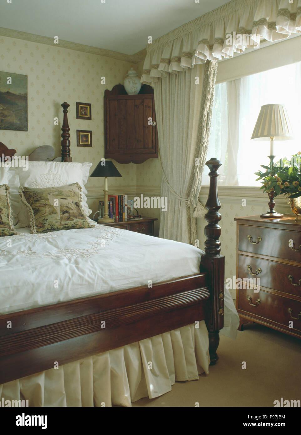 Bett aus Holz mit gedrechselten Spindeln in kleinen Schlafzimmer mit ...