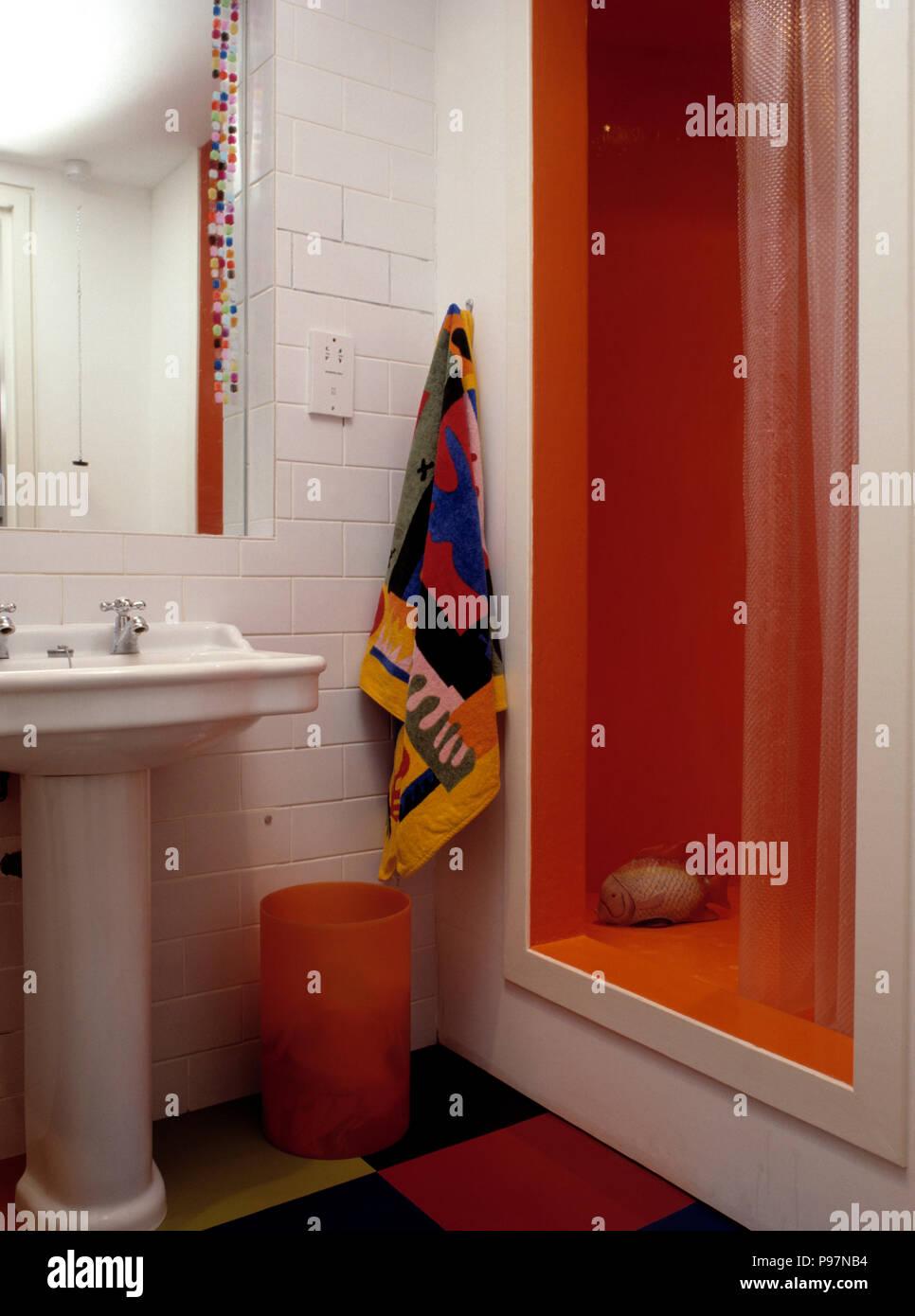 Buntes Handtuch auf weißen Fliesen Wand neben orange Dusche ...