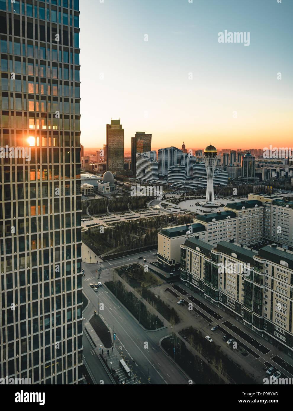 Sonnenuntergang in Richtung Bayterek Tower und Haus der Ministerien in Astana Kasachstan an einem klaren Tag Stockbild