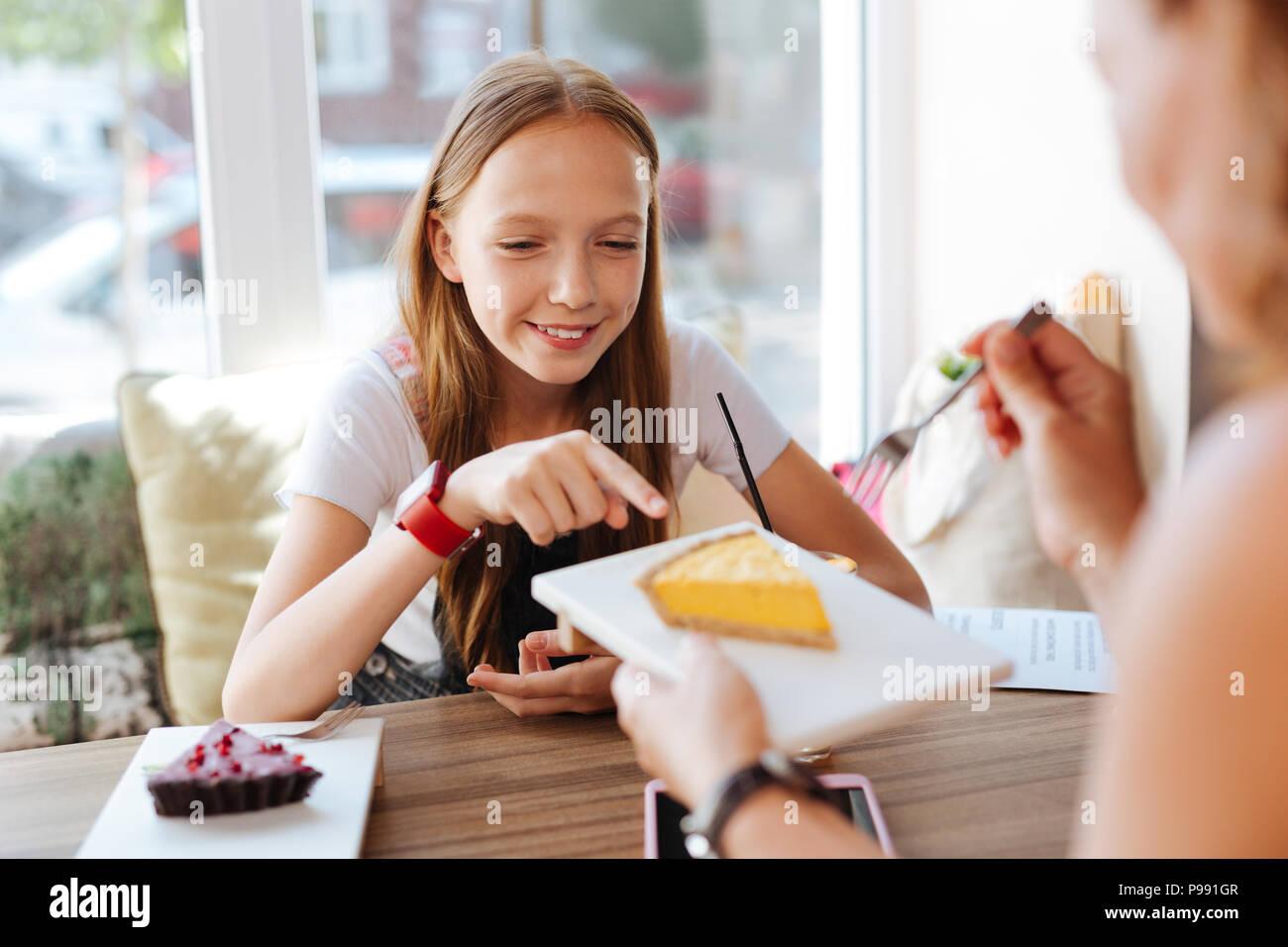 Lächelnd Teenager versuchen, Käsekuchen mit ihrer Mutter Stockbild