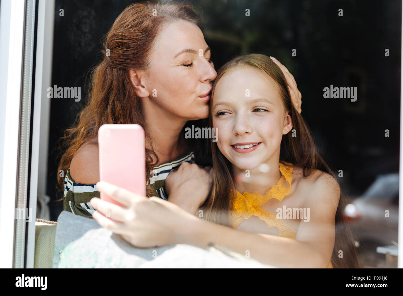 Lieben schöne Mutter küssen ihre liebevolle Tochter Stockbild