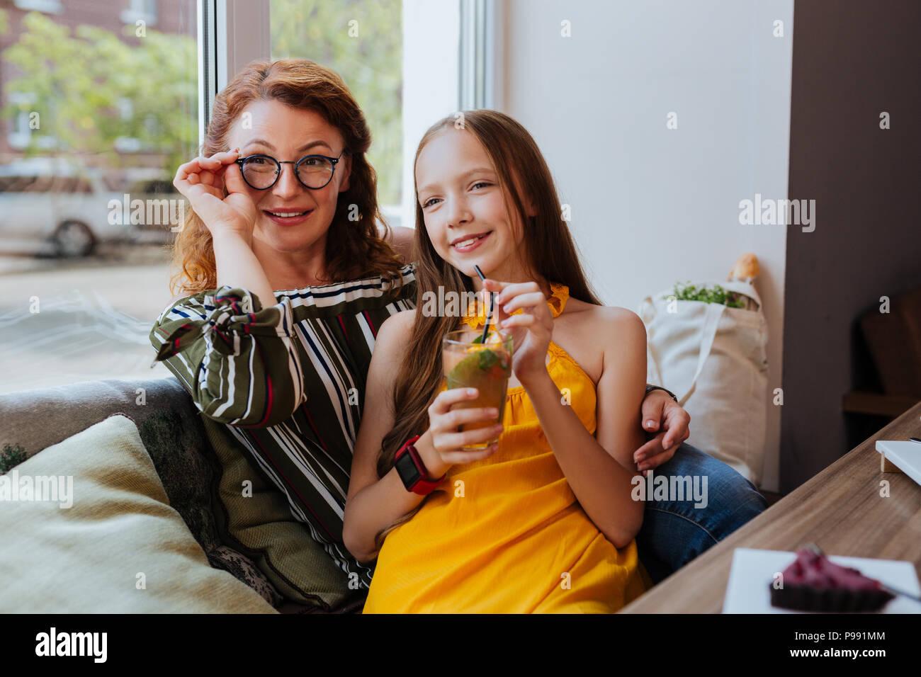 Rothaarige Mutter Brille trägt ihre angenehmen Mädchen umarmt Stockbild