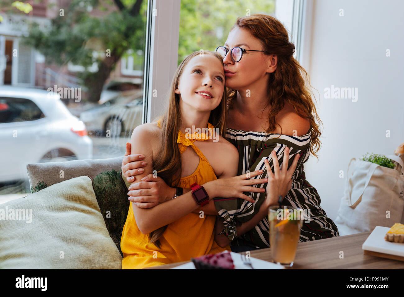 Pflege stilvolle Mutter küssen ihre attraktive Mädchen Stockbild