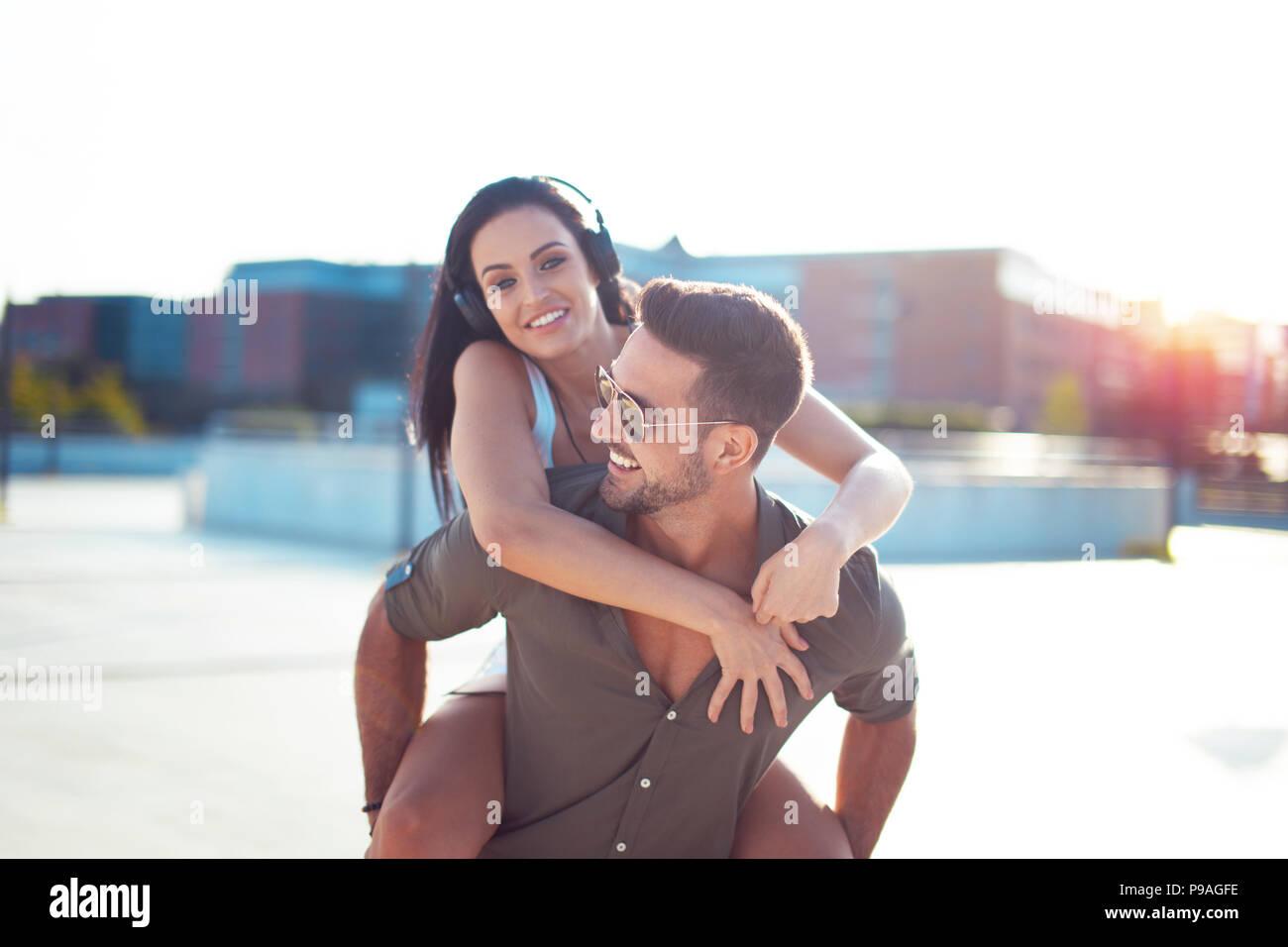 Glückliche junge trendige Urban Paar viel Spaß in Stadt, Huckepack Reiten Stockbild