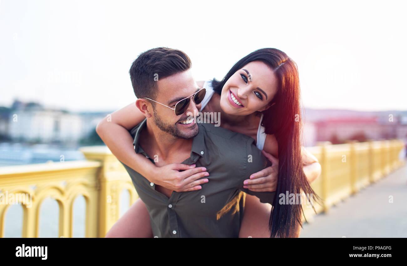 Happy brunette Frau reiten Huckepack auf Freund, Spaß Stockbild