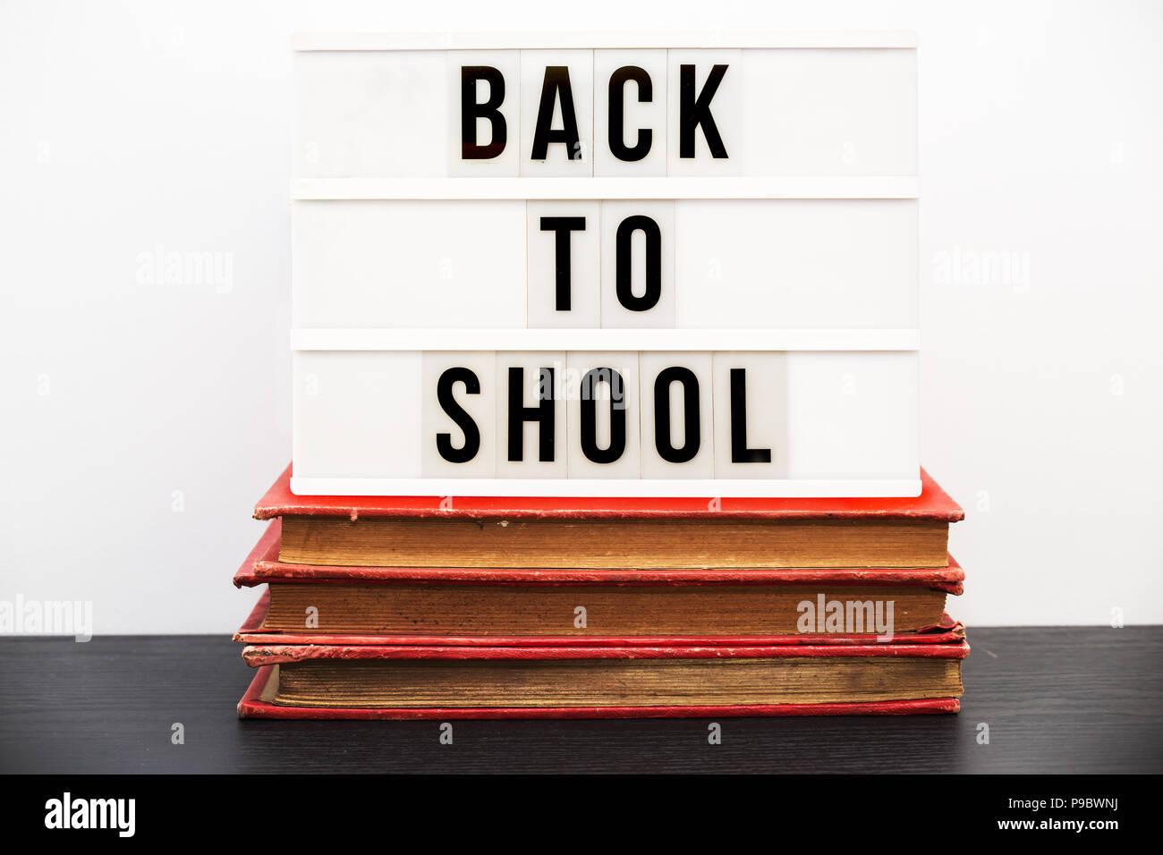 17cbe34533fe0 Zurück zu Schule in einem Leuchtkasten auf einem Stapel alter Bücher  geschrieben Stockbild