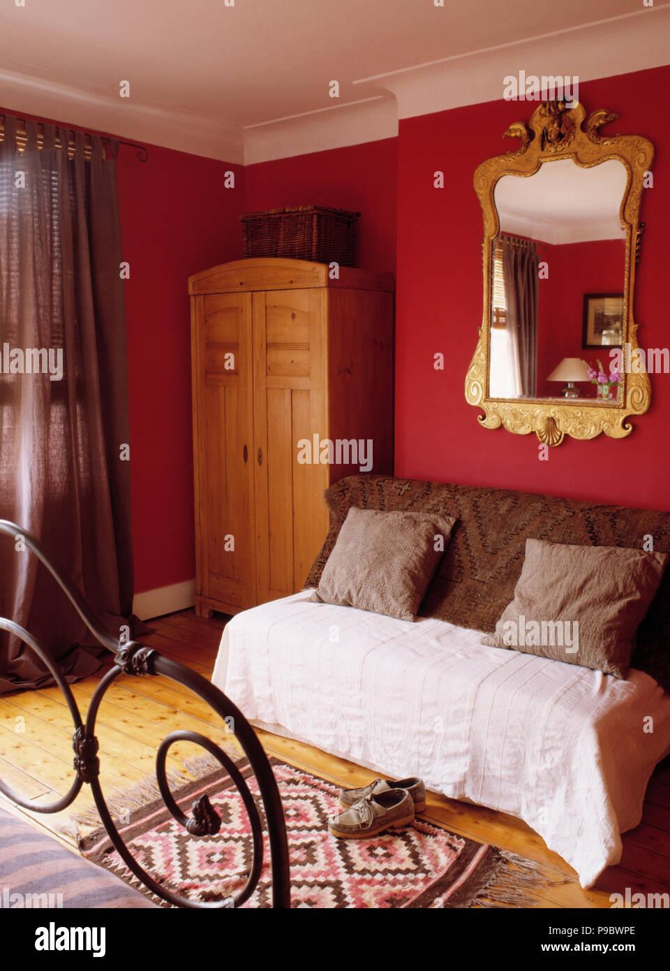 Reich verzierten vergoldeten Spiegel über Couch mit braun Kissen ...