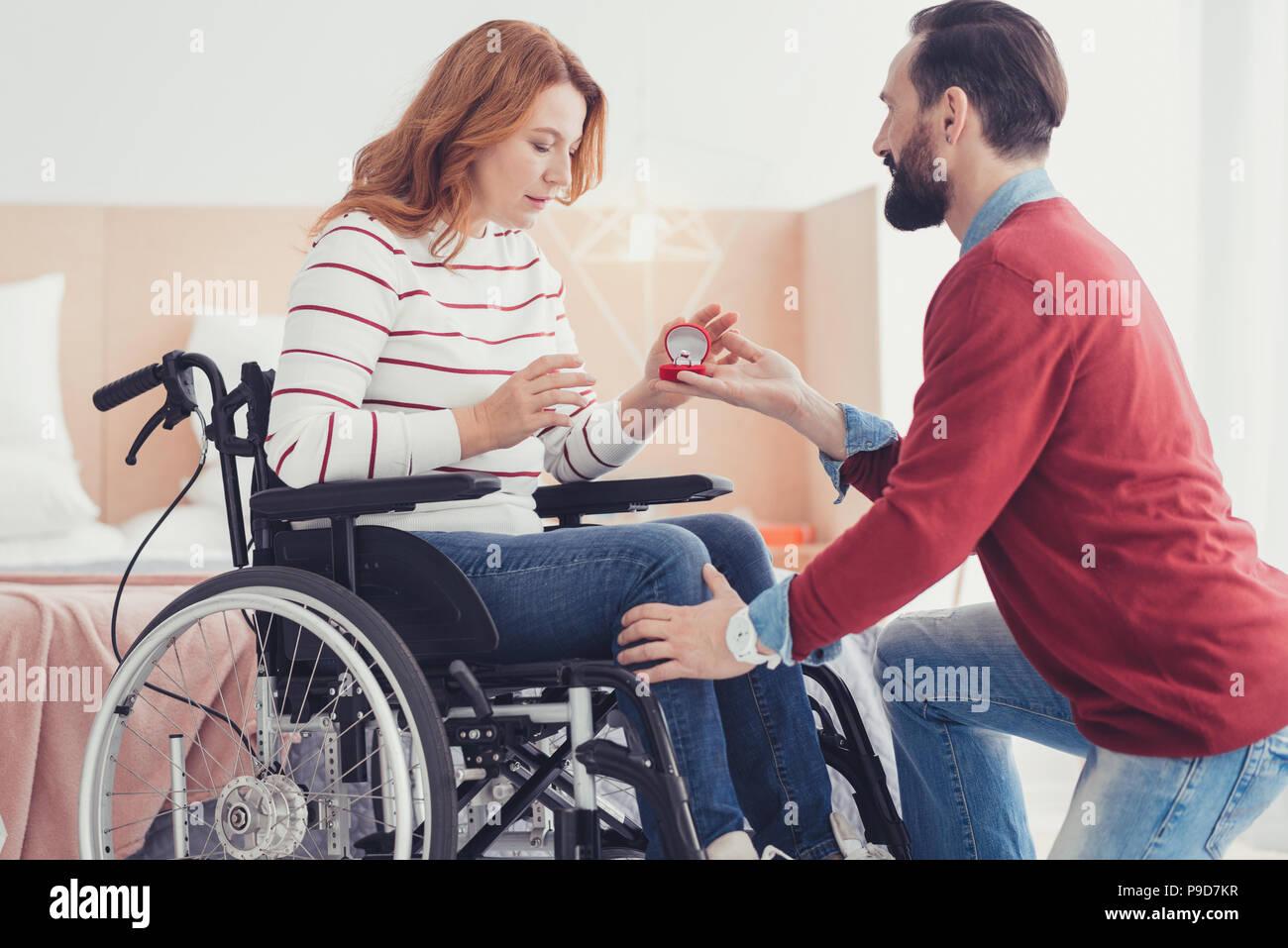 Ruhige Mann, der auf seinem Knie und bitten, seine Freundin zu heiraten Sie ihn Stockbild