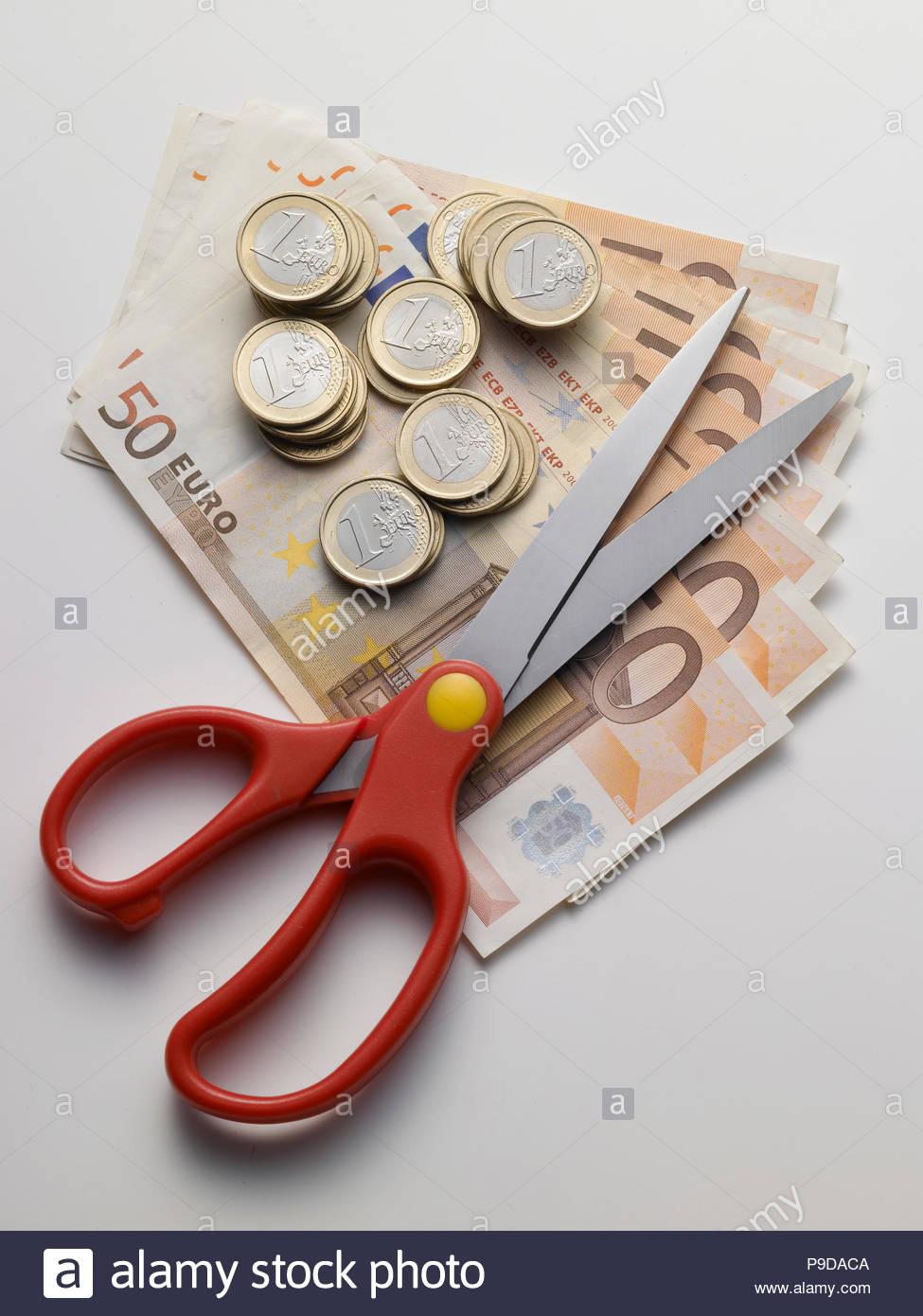 Schere und Geld auf weißem Hintergrund Stockbild