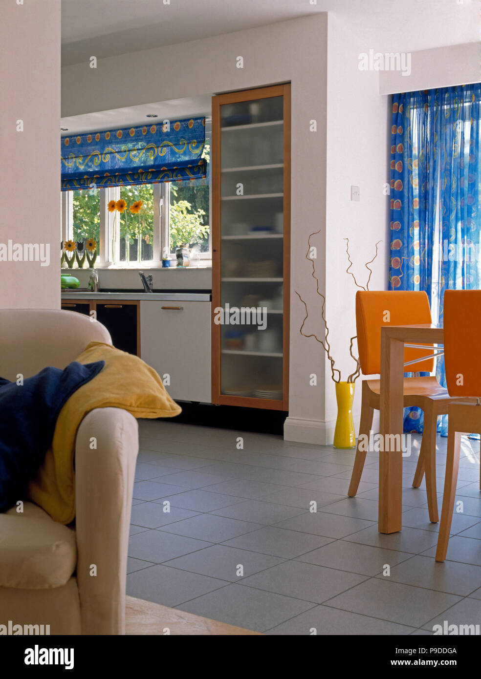 Weiss Gefliestem Boden In Eine Offene Kuche Esszimmer Mit Orangefarbenen Stuhlen Und Einen Cremefarbenen Sofa Stockfotografie Alamy