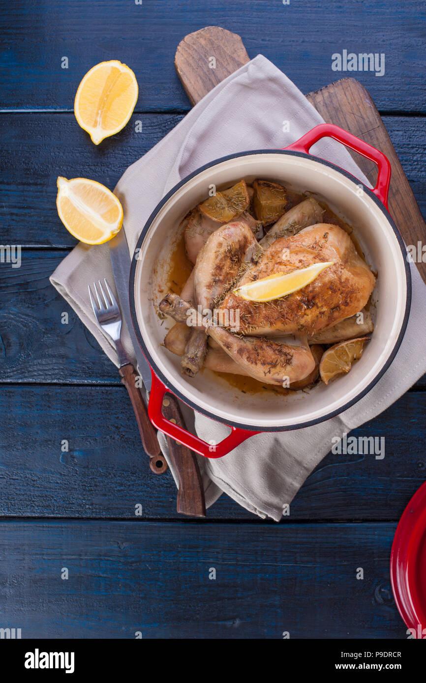Das ganze Huhn gebacken mit Zitrone und Rosmarin in einer roten Gusseisen. Blau Holz- Hintergrund und grau Handtuch. Messer und Gabel. Freier Platz für Text Stockbild