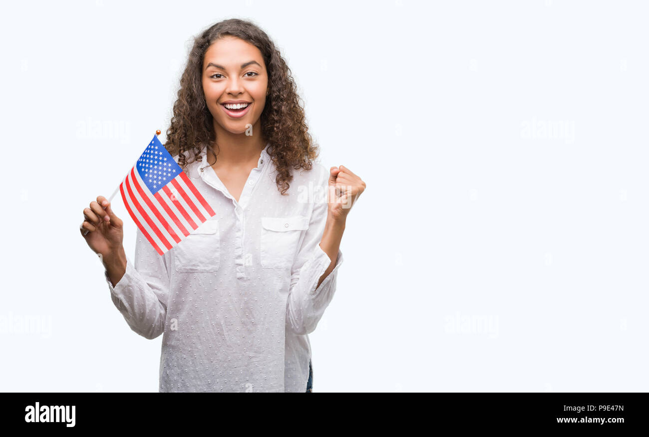Junge Hispanic woman holding Flagge der Vereinigten Fincas von Amerika schreien stolz und feiern Sieg und Erfolg sehr aufgeregt, jubelnde Emotion Stockbild