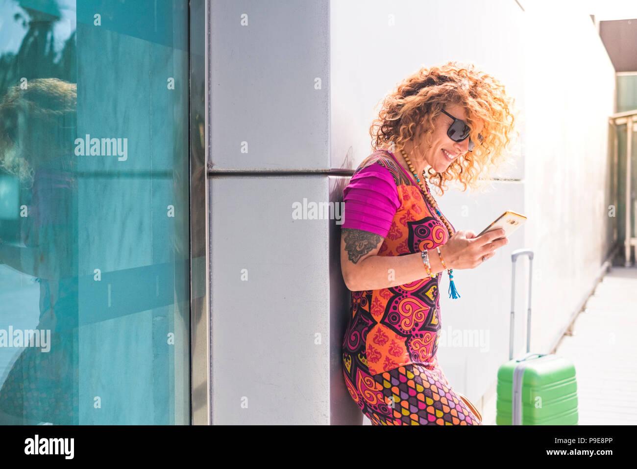 Schöne junge Frauen außerhalb des Flughafens mit Handy mit Internet Messaging. stehend mit Gepäck. Business- oder Urlaubsreise Konzept fo Stockbild