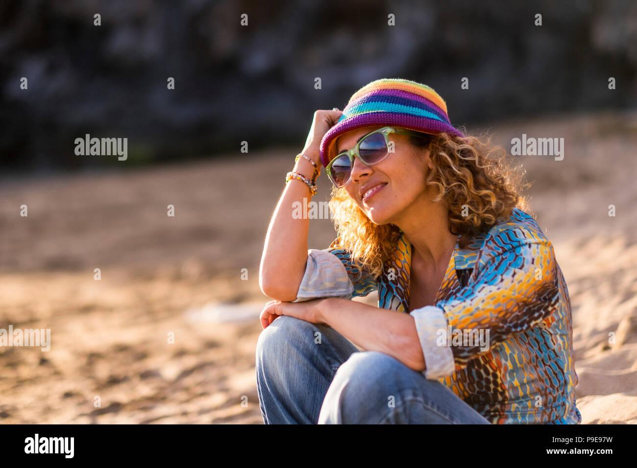 Hübsche blonde junge Frau setzen Sie sich auf den Sand am Strand entspannen und genießen den Sonnenuntergang und sonnigen Tag Urlaub. Bleiben Sie gut in einem natürlichen Platz und o Stockbild