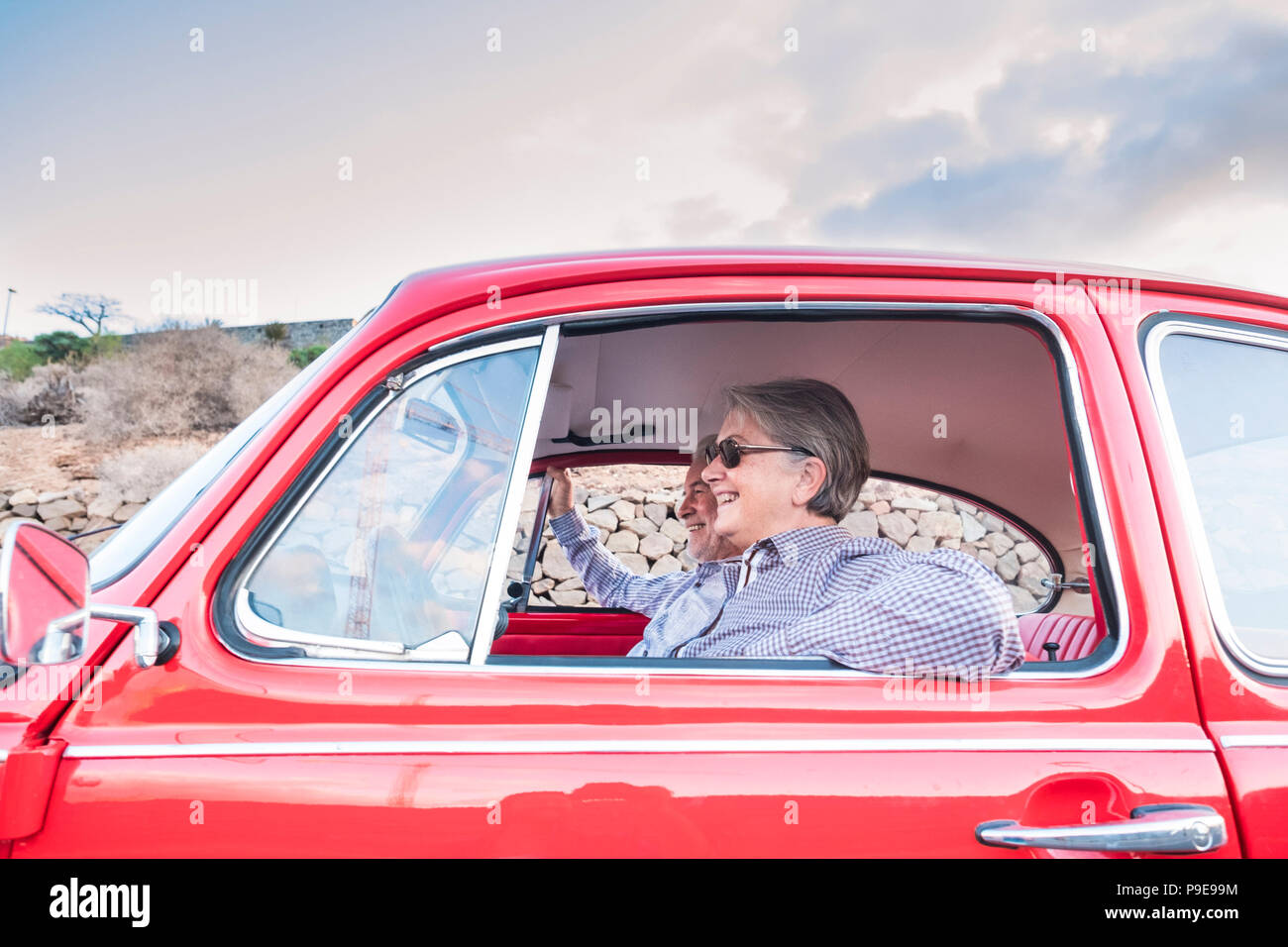 Ältere Paare mit Hut, mit Brille, mit grauen und weißen Haaren, mit casual Shirt, auf Vintage rotes Auto im Urlaub Zeit und genießen das Leben. Mit einem Chee Stockbild