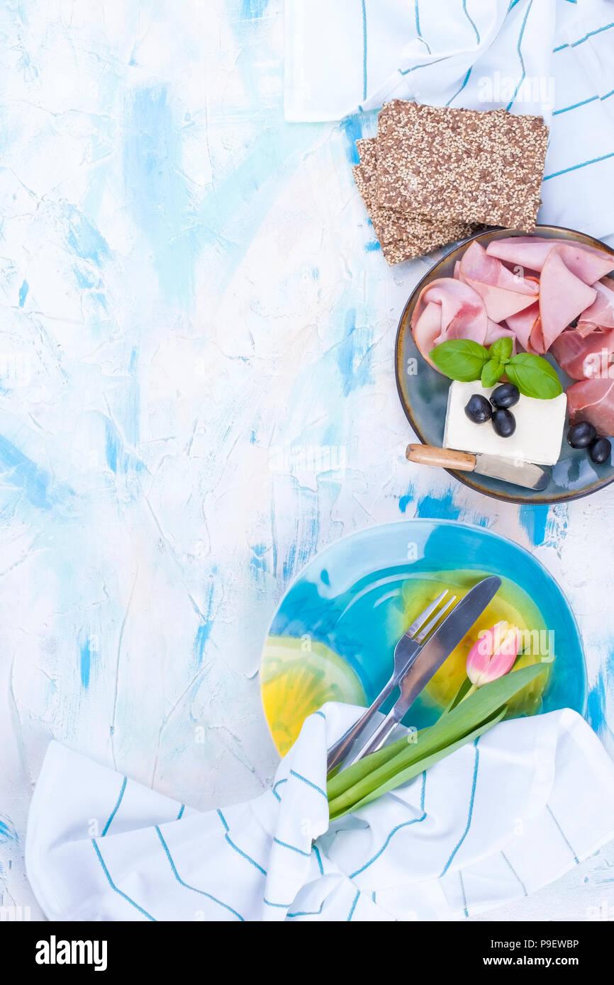 Käse und Schinken mit Oliven auf einem grauen Platte und Basilikum. Weißer Hintergrund mit blauen Scheidungen. Messer für Käse. Trockene Breadstones. Blaue Platte zum Mittagessen. Freier Platz für Text oder eine Postkarte. Stockbild