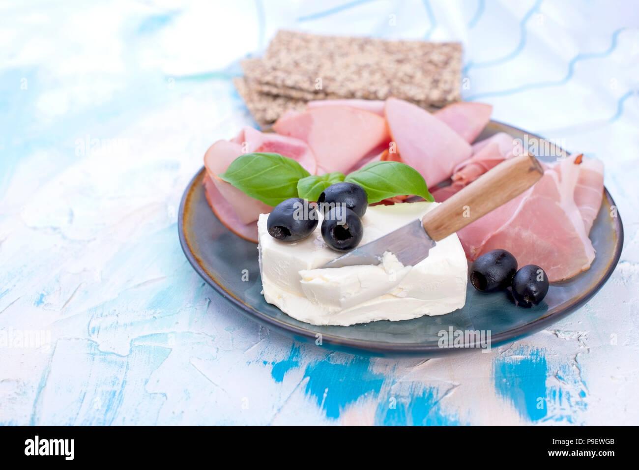Käse und Schinken mit Oliven auf einem grauen Platte. Weißer Hintergrund mit blauen Scheidungen. Messer für Käse. Trockene Breadstones. Freier Platz für Text oder eine Postkarte. Stockbild