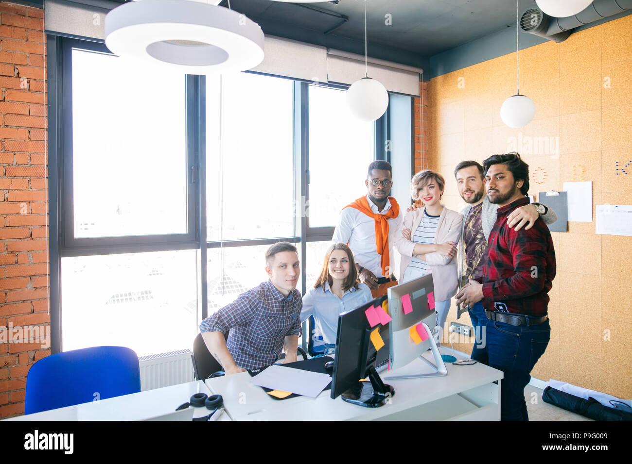 Foto von wunderschöne junge startup Team auf die Kamera in der Loft office posieren. super multi-ethnische junge Menschen bei der Arbeit Stockbild