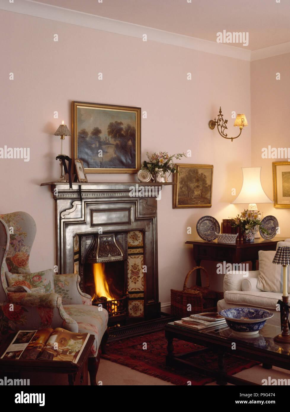 Ohrensessel Neben Brennenden Feuer In Schwarzen Gusseisernen  Viktorianischen Kamin Im Kleinen Wohnzimmer Mit Beleuchteten Lampe Am Tisch  In Der Ecke Der ...