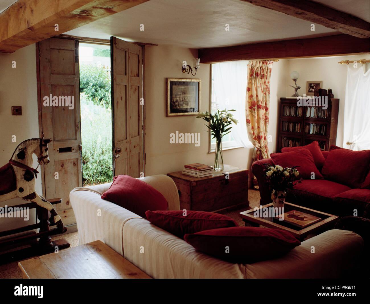 Rotes Sofa In Ferienhaus Wohnzimmer Mit Roten Kissen An Den Cremefarbenen Sofa Neben Doppel Kiefer Turen Zum Garten Stockfotografie Alamy