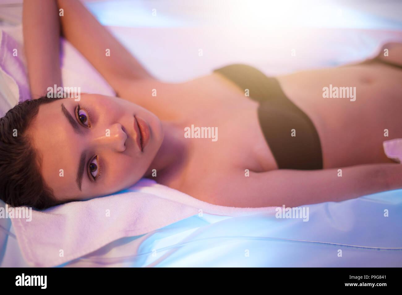 Eine Quelle von Energie. Gut aussehende Mädchen mit schwarzen Haaren liegen auf dem modernen Sonnenbank Stockbild
