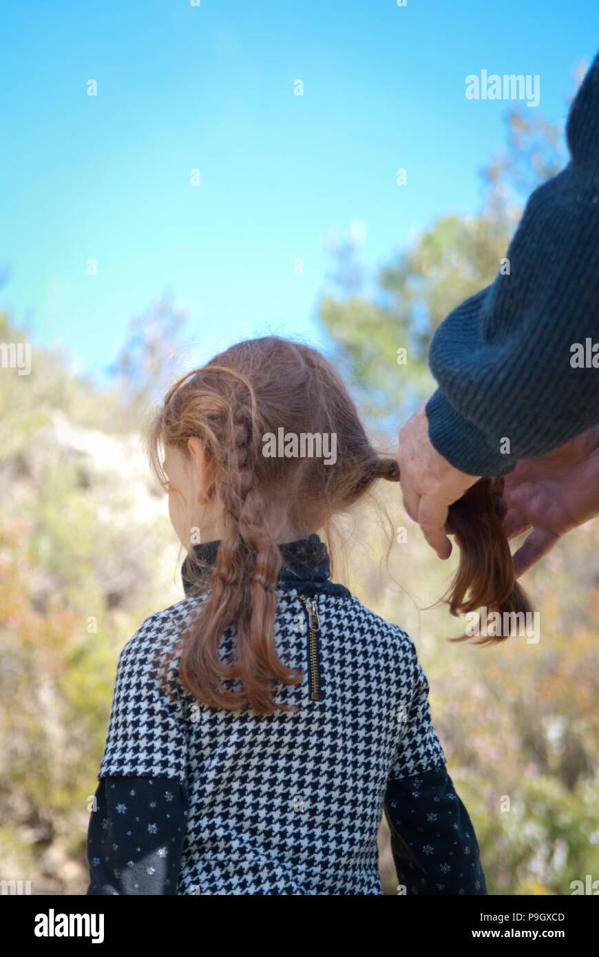 7/8-Ansicht von einem Vater Bindematerial, Rote lange Haare. Seine vier Jahre alte Tochter außerhalb mit Bäumen im Hintergrund Stockbild
