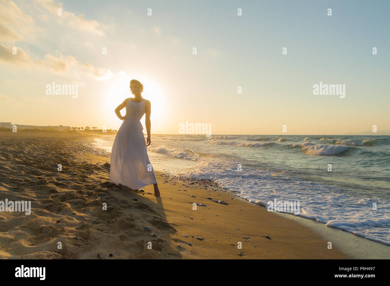 Frau in weißem Kleid, barfuss, Gefühl glücklich, lebendig und frei in der Natur meditieren am sandigen Misty Beach atmen saubere frische Meeresluft in der Abenddämmerung. Sommer Urlaub lifestyle Konzept Stockbild