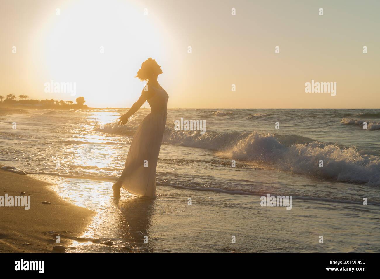 Frau mit Arme angehoben, barfuss, Gefühl glücklich, lebendig und frei in der Natur meditieren am sandigen Misty Beach atmen saubere frische Meeresluft in der Abenddämmerung. Sommer Urlaub lifestyle Konzept Stockbild