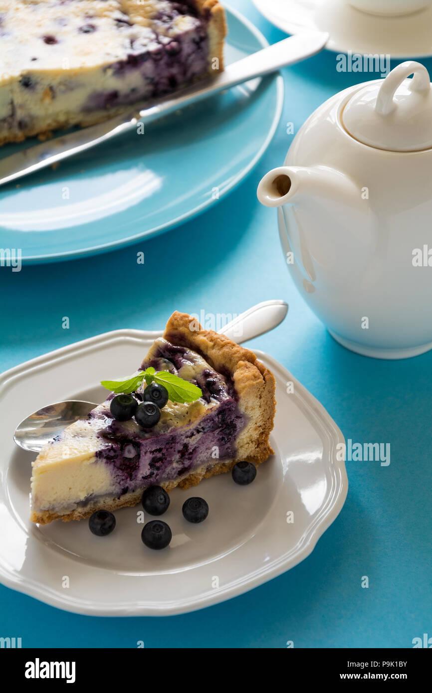 Tea Time. Hausgemachten blueberry Cheesecake mit Ricotta auf blauem Papier Hintergrund Stockbild