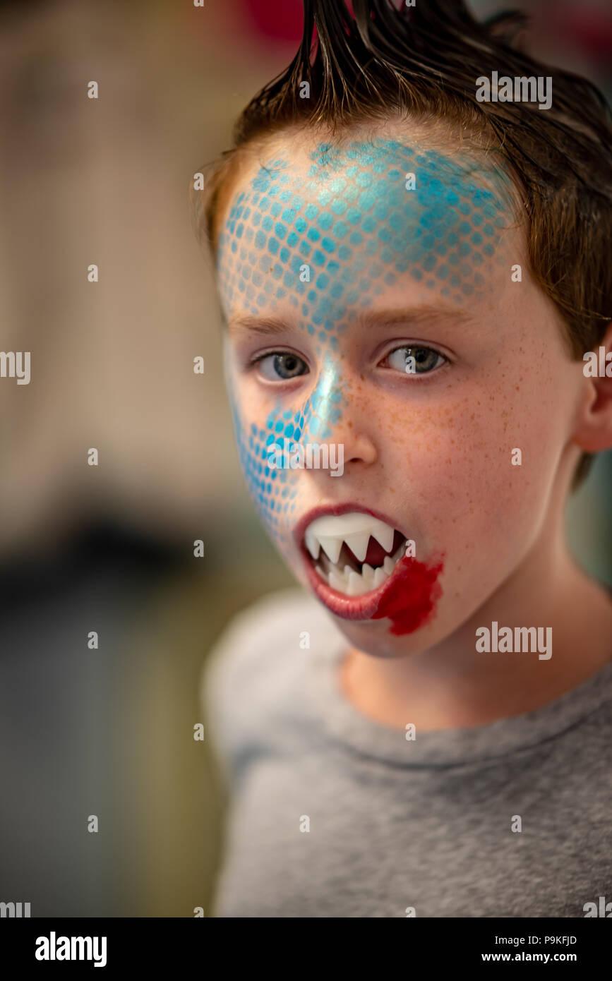 Junge mit Gesicht wie ein Hai bemalt Stockbild