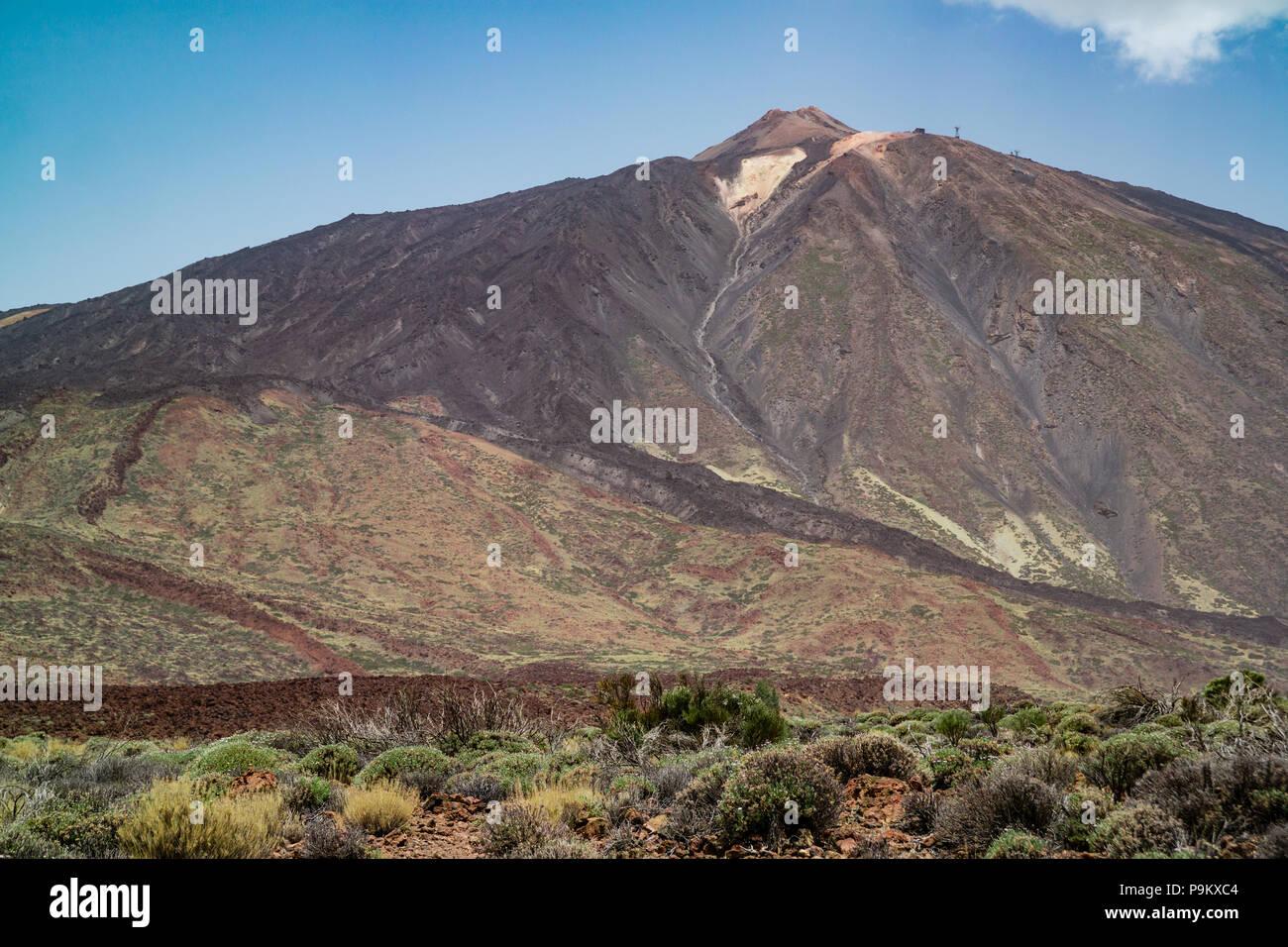 Mount Teide, ein Jahrzehnt Vulkan in Teneriffa, mit trockenen Buschland und Lavagestein im Vordergrund der Landschaft. Stockbild