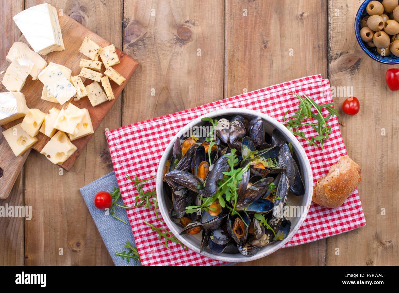 Müsli in einem weißen Keramik Schüssel, auf einem roten Serviette. Käse auf einem Holzbrett und einem Glas Wein und Oliven. Auf einer hölzernen Hintergrund. Freier Platz für Text oder Werbung Stockbild